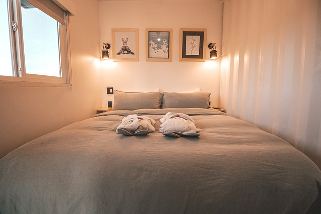 Úzká ložnice s velkou postelí a rozsvícenými lampičkami připevněnými ke zdi